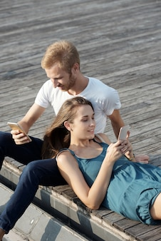 Красивый молодой человек читает статью на смартфоне, когда подруга держит голову ему на коленях и проверяет ...