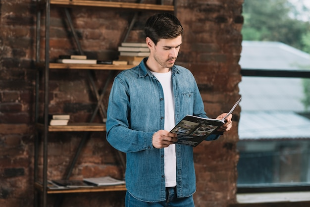 Handsome young man reading magazine standing in front of book shelf