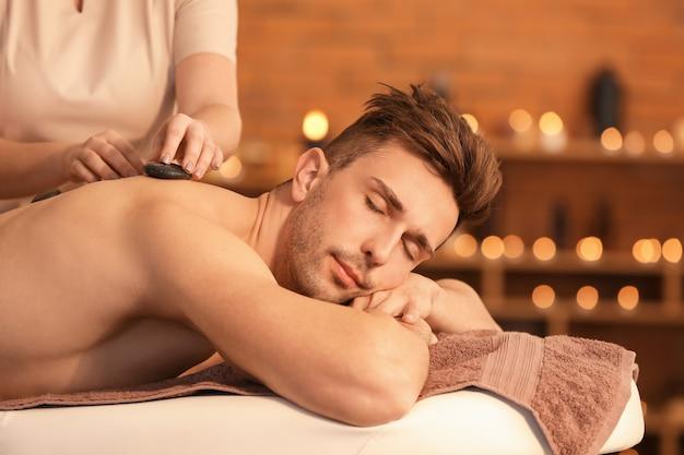 Красивый молодой человек, получающий массаж в спа-салоне
