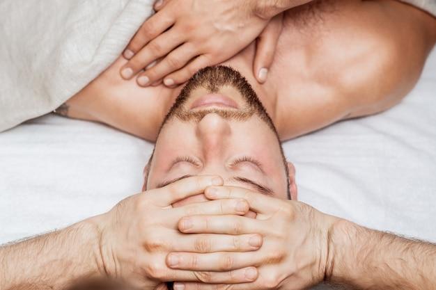健康スパセンターで2人のマッサージ師の4つの手によってリラックスできるヘッドマッサージを受けるハンサムな若い男