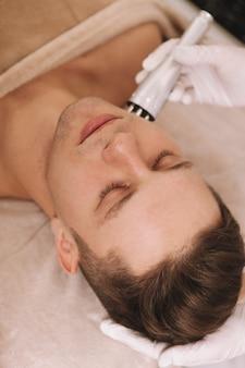 ビューティーサロンでスキンケア治療を受けるハンサムな若い男