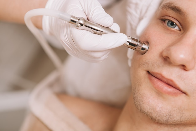Handsome young man receiving skincare treatment at beauty salon