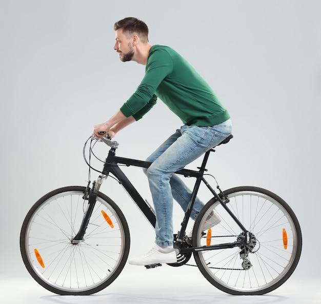 光で自転車に乗るハンサムな若い男