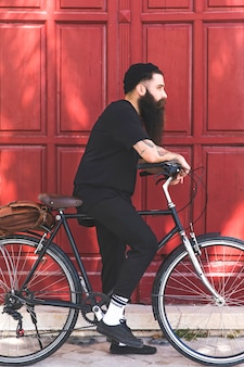 Handsome young man riding bicycle outdoors on sunny day