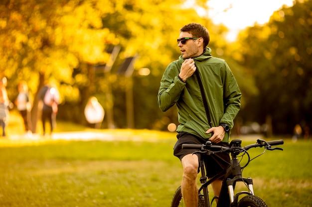 公園で電動自転車に乗ってハンサムな若い男