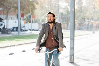 Handsome young man riding his bicycle in the park