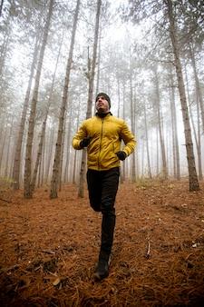 秋の森を走り、トレイルランマラソン耐久レースのために運動しているハンサムな若い男