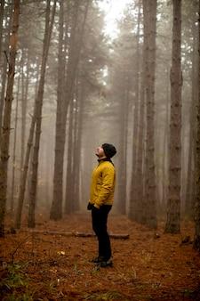 Красивый молодой человек работает в осеннем лесу и тренируется для марафонской гонки на выносливость