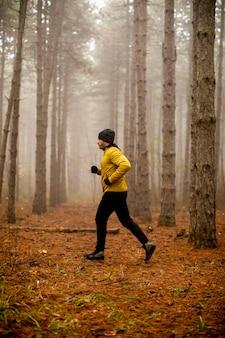 Красивый молодой человек работает в осеннем лесу и тренируется в марафонской гонке на выносливость