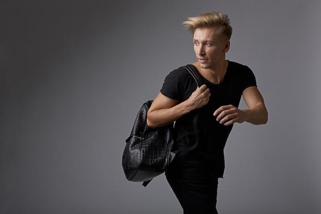 Красивый молодой человек работает с рюкзаком на плечах