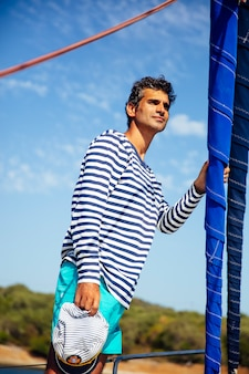 Handsome young man on a sailboat