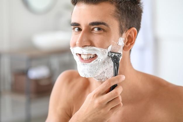 Красивый молодой человек бреется дома