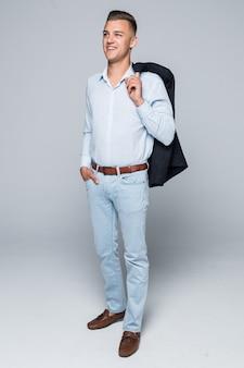Bel giovane uomo in camicia e jeans tiene la giacca sulla spalla isolata sul muro grigio chiaro