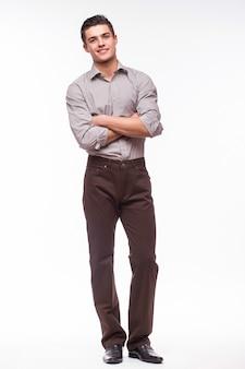 Bel giovane uomo in camicia mentre in piedi contro il muro bianco