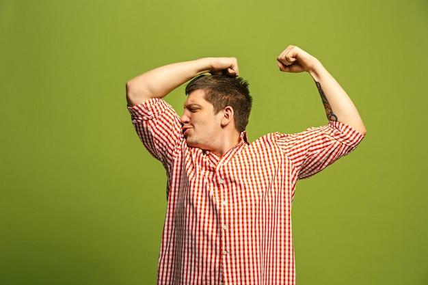 強さとジムのコンセプトを表現する上腕二頭筋を示すハンサムな若い男、健康的な生活はその良いです。スタジオに立っている若い感情的な驚きの男
