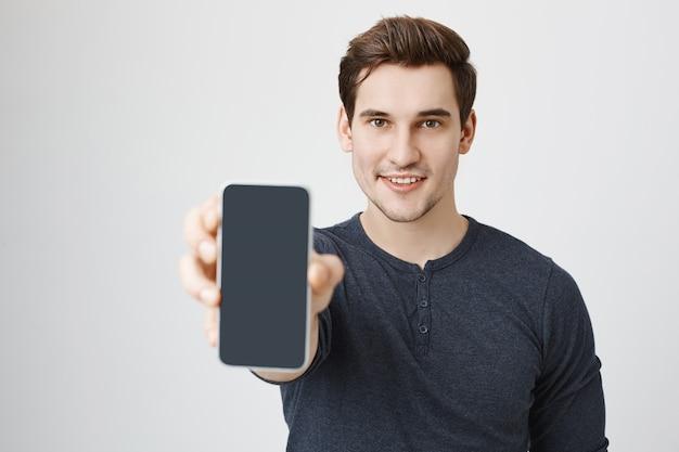 Bel giovane che mostra il display del telefono cellulare