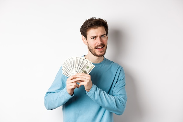 Handsome young man showing money and looking pleased. guy dancing with dollars, earn income, standing over white background.