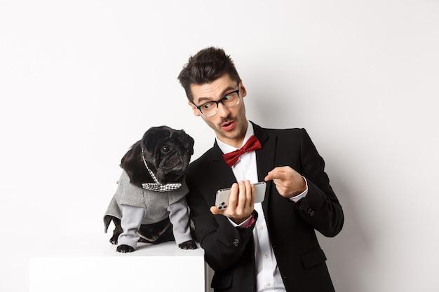 그의 개에 휴대 전화에 뭔가 보여주는 잘생긴 젊은 남자. 흰색 배경 위에 의상을 입고 서 있는 애완동물과 온라인 쇼핑을 하는 소유자