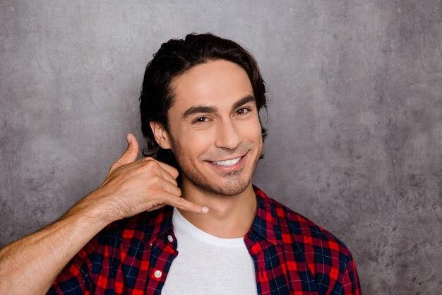 Красивый молодой человек показывает жест пальцами «позвони мне»