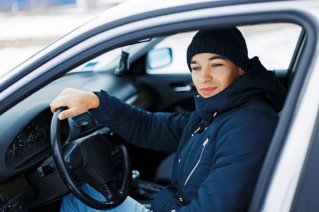 잘 생긴 젊은 남자가 차에 앉아 바퀴를 보유