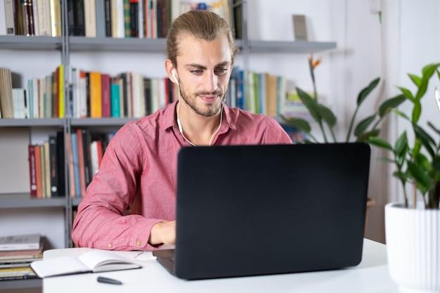 Красивый молодой человек сидит за столом у себя дома, работая с ноутбуком и наушниками