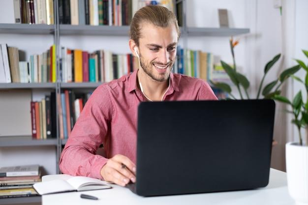 ラップトップとヘッドフォンで作業している自宅のテーブルに座っているハンサムな若い男
