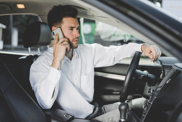 Handsome young man sitting in car talking on mobile phone