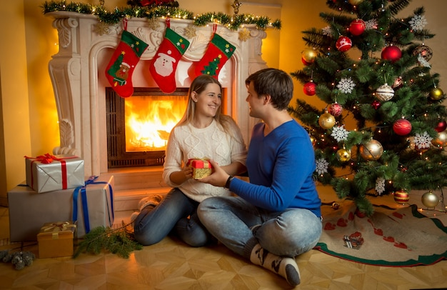 Handsome young man sitting at fireplace with woman and giving her christmas present