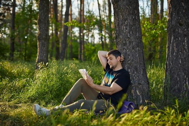 Красивый молодой человек сидит в лесу на траве, прислонившись к дереву, читает книгу