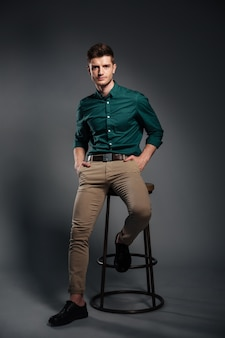 Handsome young man sitting isolated over grey