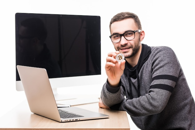 Handsome young man sitting at office place with laptop and screen of monitor on his back pointed bitcoin on white