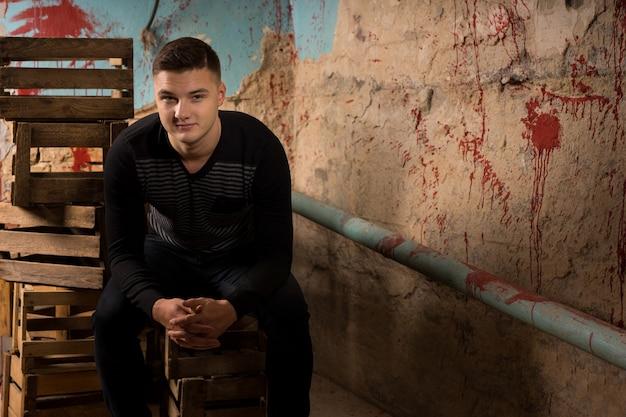 할로윈 공포 컨셉의 끔찍한 지하실에서 빈 포장 상자에 앉아 있는 잘생긴 청년