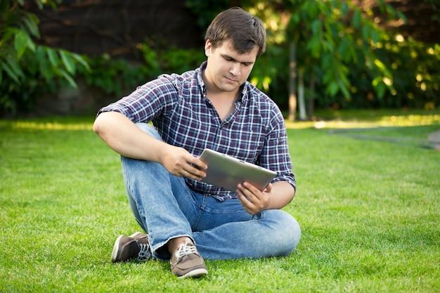 ハンサムな若い男が公園の芝生の上に座って、デジタル タブレットを使用して