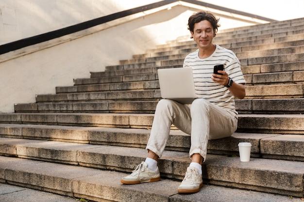 ラップトップコンピューターと携帯電話を使用して屋外の階段に座っているハンサムな若い男。