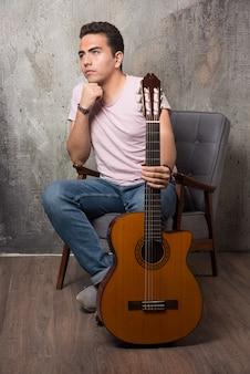 ギターを保持しながら椅子に座っているハンサムな若い男。