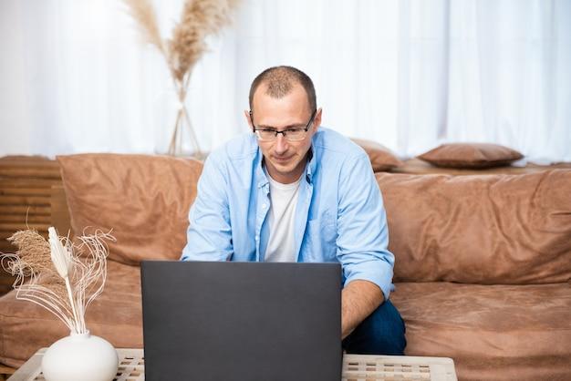 Красивый молодой человек сидит на диване и работает на ноутбуке