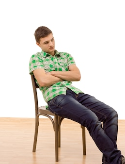 Красивый молодой человек сидит в деревянном стуле