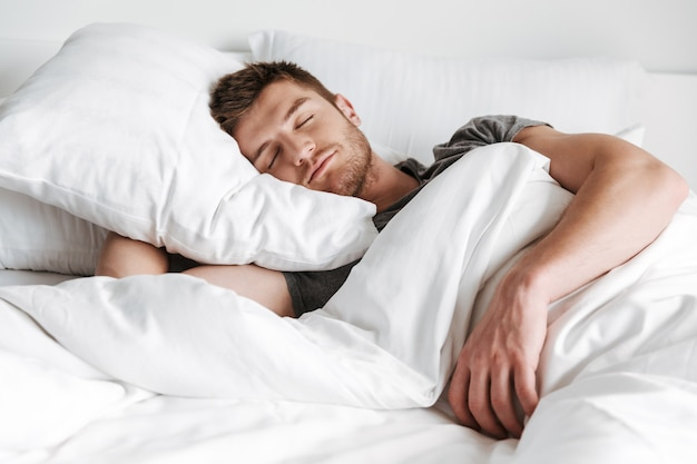 Handsome young man sleeping in bed