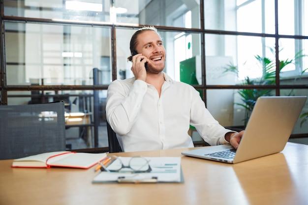 Красивый молодой человек улыбается и разговаривает по мобильному телефону во время работы с ноутбуком