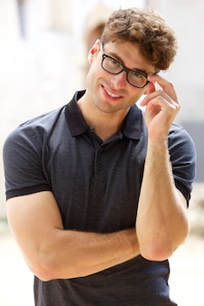 Handsome young man smiling with glasses outdoors