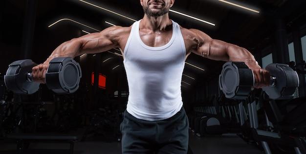 Красивый молодой человек разводит руки с гантелями в стороны. прокачка плеча. концепция фитнеса и бодибилдинга. смешанная техника
