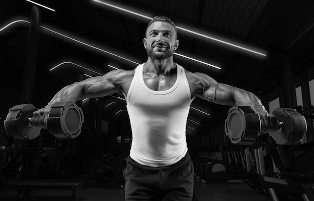 Красивый молодой человек разводит руки с гантелями в стороны. прокачка плеча. концепция фитнеса и бодибилдинга.