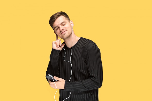 The handsome young man standing and listening music.