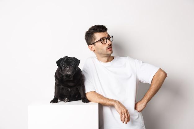 Красивый молодой человек, стоящий рядом с симпатичным черным мопсом, глядя прямо с высокомерным выражением лица, стоит над белой