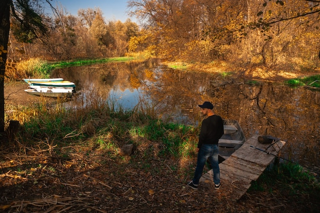 Handsome young man stands on the river bank in autumn