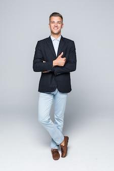 Красивый молодой человек студент-бизнесмен в куртке держит скрещенными руками, изолированными на светло-серой стене