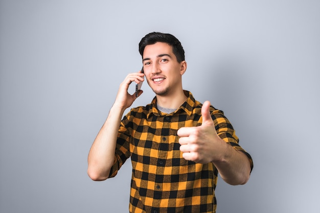 Handsome young man or student in yellow shirt with smile on face gets good news by phone and shows like sign, big thumb up