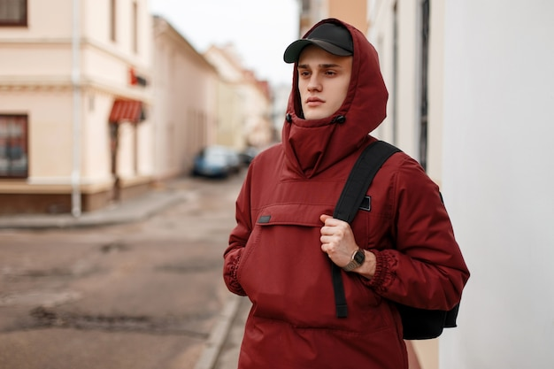 Handsome young man in a stylish red long jacket with a hood in a trendy cap with a black backpack walks around the city near vintage houses