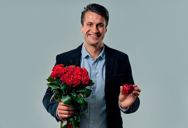 Handsome young man in suit is posing on grey with ring and red roses in hands, looking at camera and smiling.