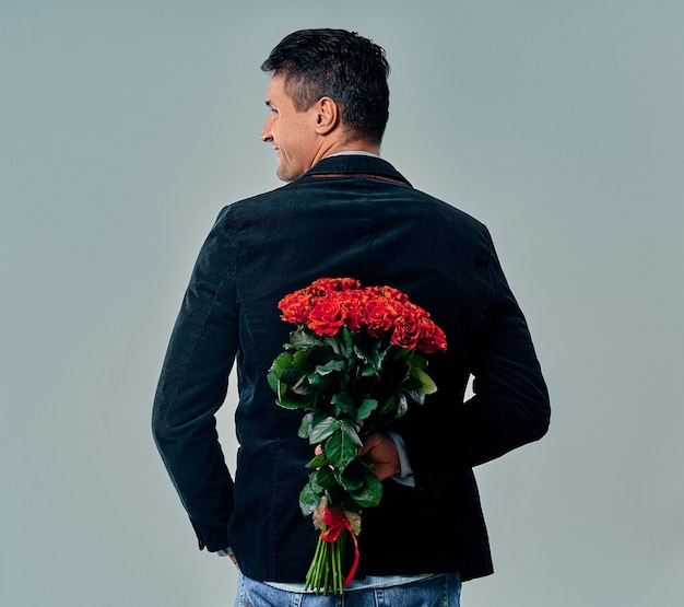 Handsome young man in suit is standing with red roses behind the back on grey.